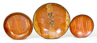 Three Slip-Decorated Redware Plates, Pennsylvania origin, early to mid 19th century