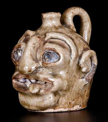Outstanding Edgefield Discovery. Exceedingly Rare and Important Diminutive Stoneware Face Jug with Protruding Tongue, Edgefield, SC origin, circa 1860-1880. This unusually small example includes kaolin eyes, featuring green and gold cold-painted pupils and irises, as well as unusual narrow spout construction. The figure s open mouth reveals alkaline-glazed teeth and a most unusual, protruding tongue. This example is extremely rare in overall style, and was produced by a previously undocumented school or maker. Provenance: A recently-discovered example from the same consignor as lot #209 in our October 17, 2015 auction.