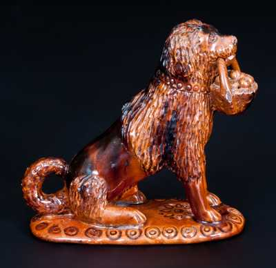 Glazed Redware Figure of a Dog with Basket, Pennsylvania origin, third quarter 19th century. This example includes excellent impressed and incised detail to the basket of apples in the dog s mouth. Provenance: A fresh-to-the-market example, purchased by the consignor in the 1960s. L 6